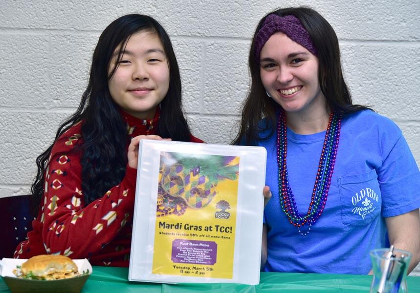 Two female smiling students at the Transylvania County Campus for Mardi Gras activity