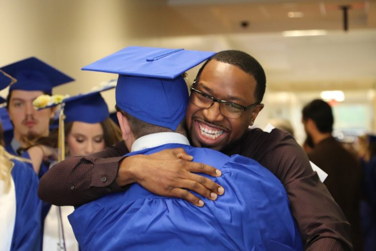 A man smiling and hugging a student dressed in a cap and gown