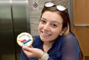 Student smiling holding up a cookie with the school logo on it that she received at welcome week