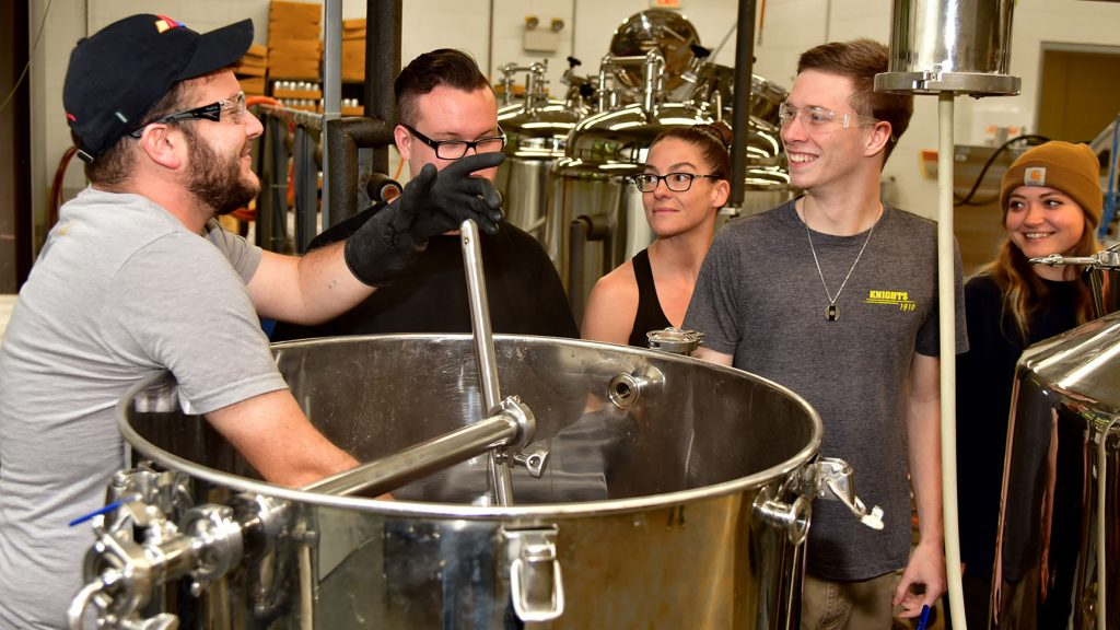 An instructor stirs a large kettle while four students look on