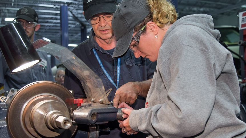 Instructor and Student turning brake rotor in auto systems class