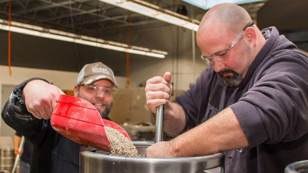 A student dumps a scoop of grain into a kettle while another stirs
