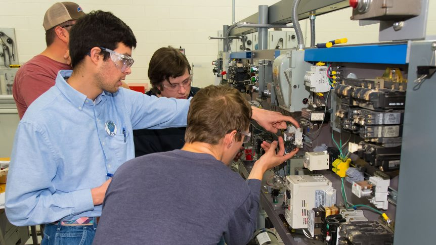 An instructor and student work on an electrical component while two other students look on