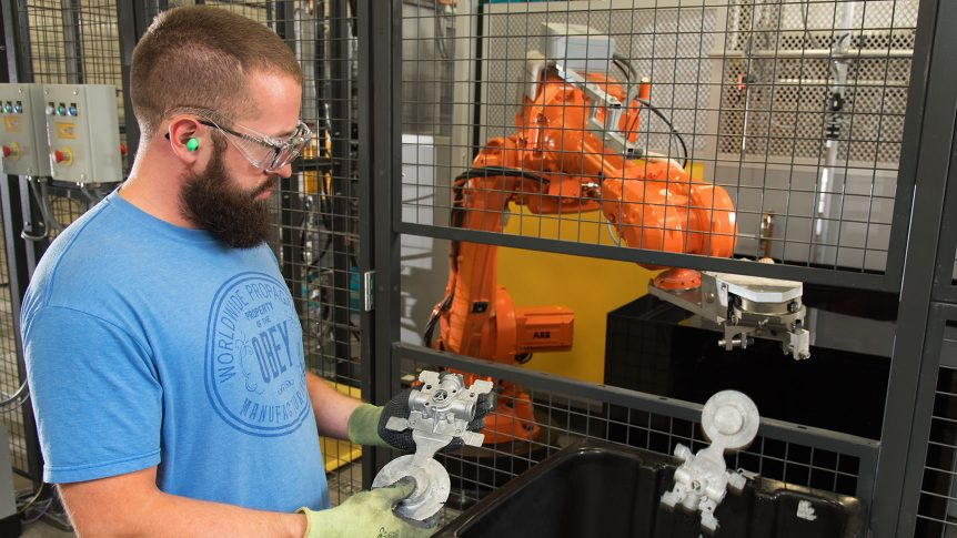 Student inspects an aluminum casting while a robotic arm drops another casting into a bin