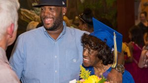 Older woman in a graduation cap and gown holding flowers with a younger man's arm around her