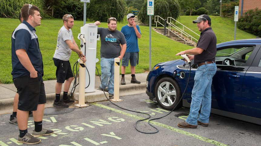 An instructor demonstrates connecting a plug-in hybrid vehicle to onlooking students