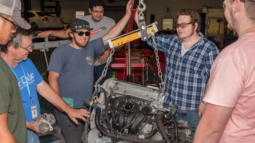 An instructor and five students stand around an engine that has been removed from a vehicle