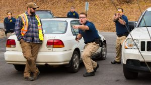Four law enforcement students in a parking lot take an active stance to a threat out of frame with guns drawn while an instructor looks on
