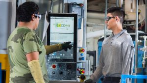 Two employees around a control screen in a manufacturing setting