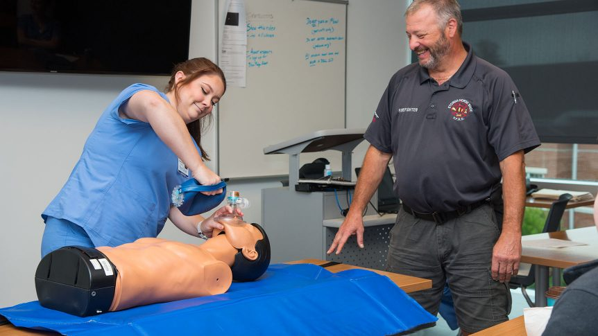 Student works on a mock patient with a breathing mask and bag while an instructor watches over her
