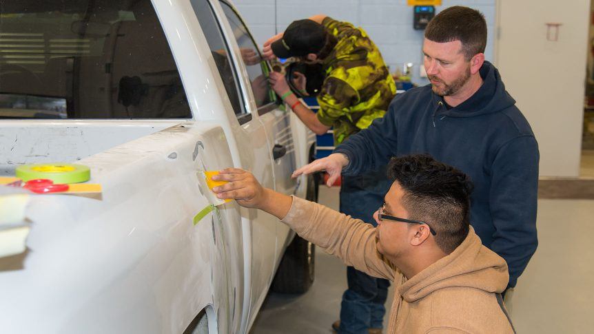 Student applies bondo to a vehicle while an instructor watches attentively