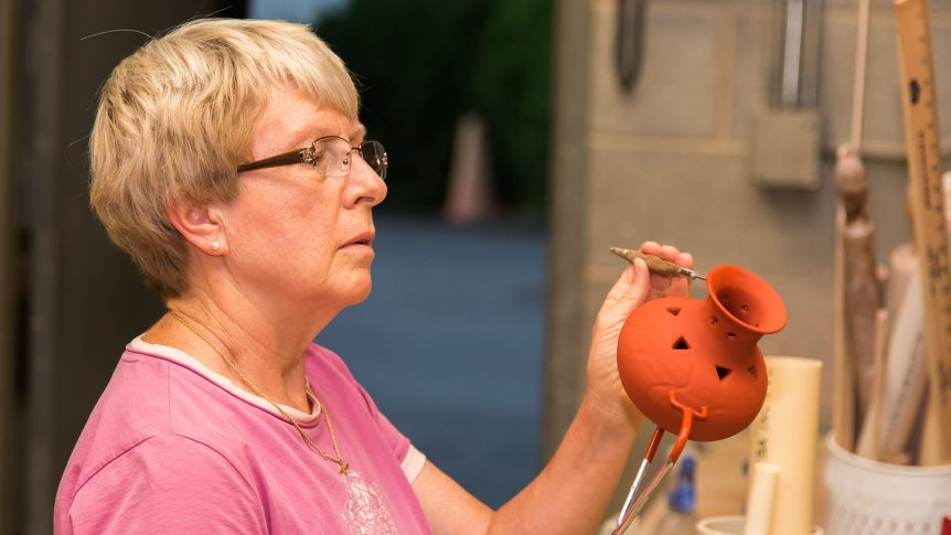 Pottery student holding a pot that has just been dipped in glaze and works on it with a small tool