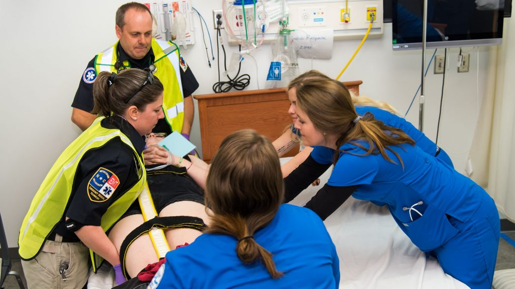 Two EMT students and three nursing students move a patient from a gurney to a bed