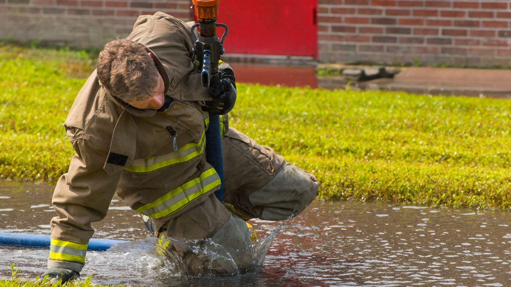 A Fire Academy student splashes through a puddle of water while advancing with a fire hose