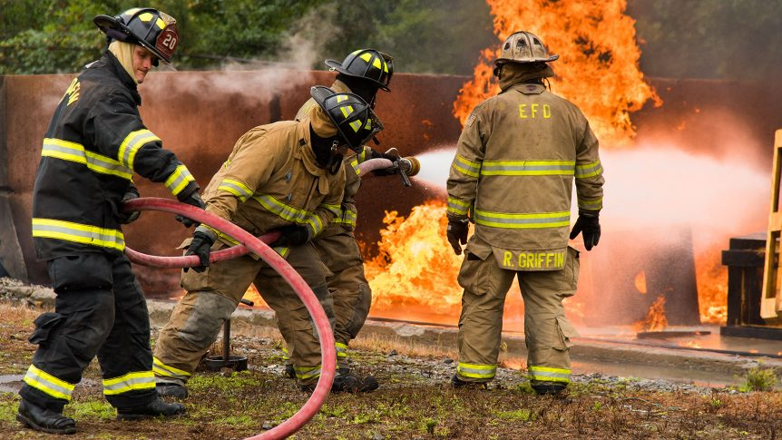 Three students handle a hose while spraying a fire in an enclosed pit with an instructor looking on