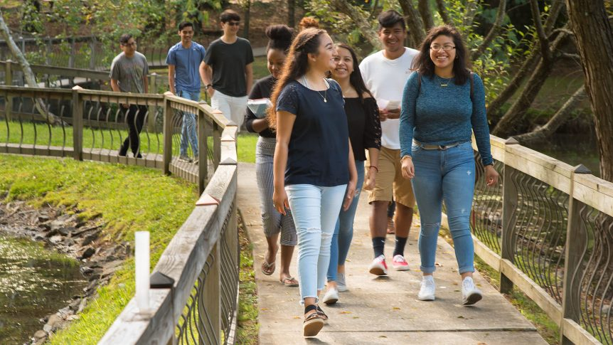 A group of students walk on the sidewalk by the lake on the Henderson County Campus