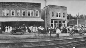 Downtown Saluda in the early 1900's looking across train tracks at a crowd of people on the streets