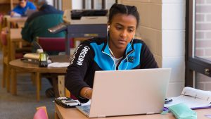 Student works on laptop in the library
