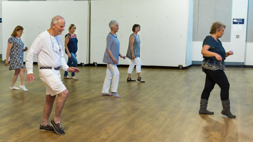 Group of five students line dancing behind an instructor