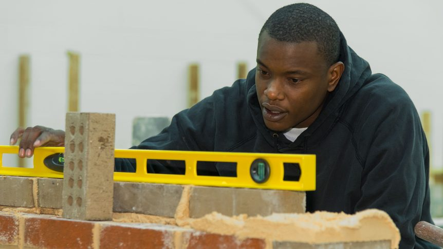 Masonry student using a level to check a brick wall he is building
