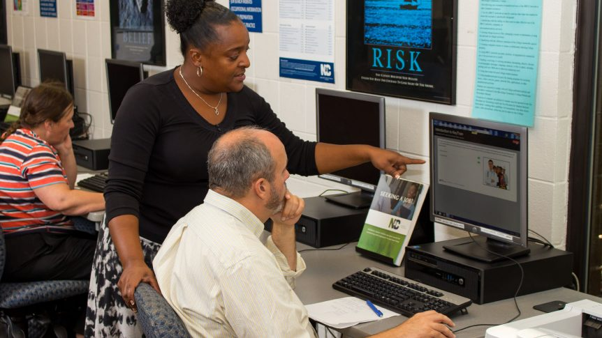 A job seeker at a computer receives help navigating a job search from an N C works employee