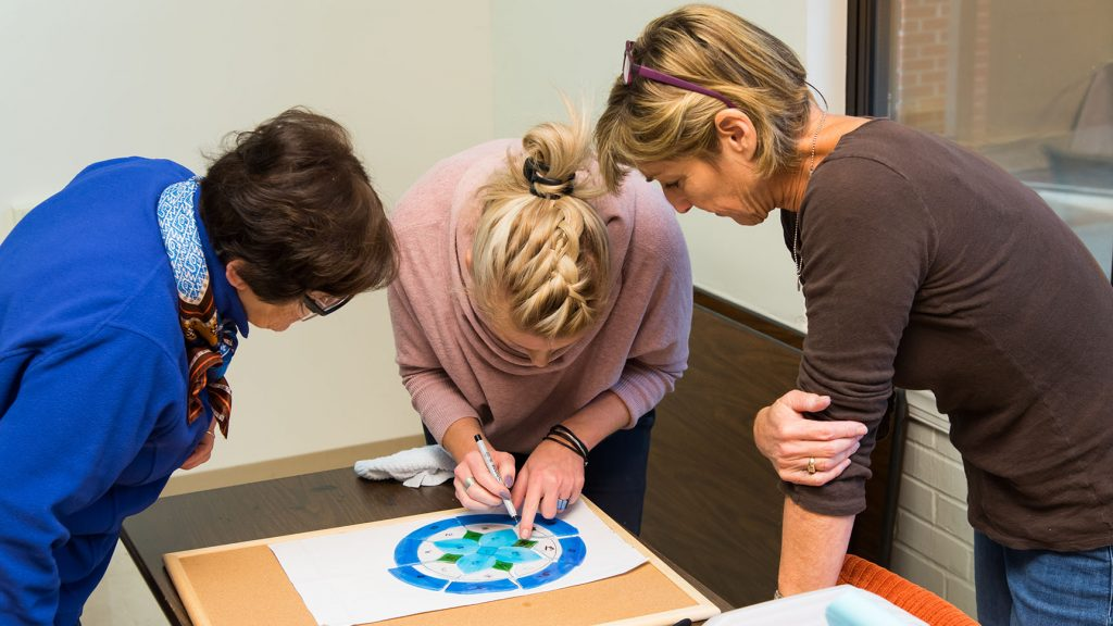 An instructor marks a stained glass layout while two students look on