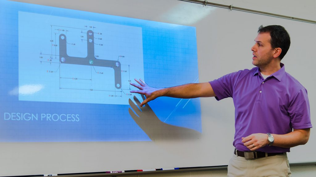 a student discusses his design process while referencing a schematic on a projection screen at the front of a classroom