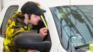 A student tapes up a window on a vehicle in preparation for painting