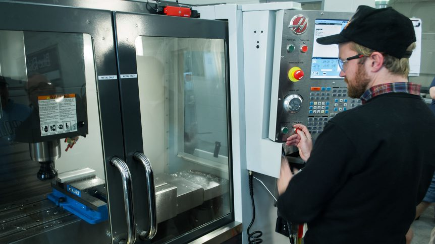 Student operates the control panel of a C N C machining mill