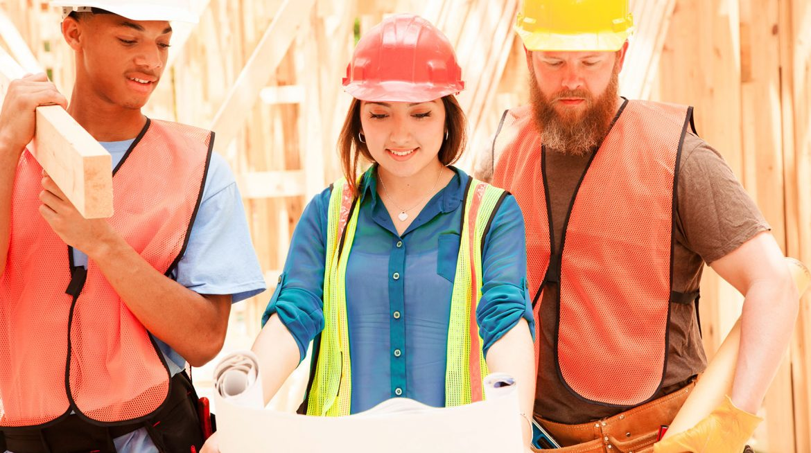 Three construction workers look at plans