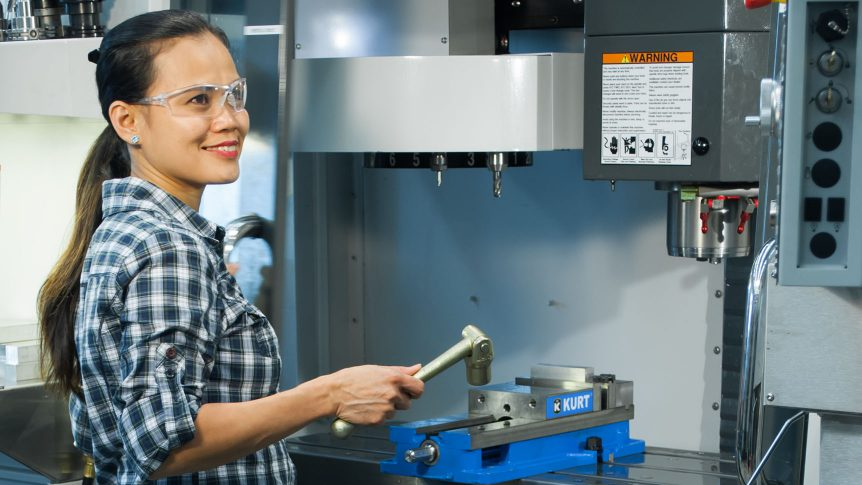 A woman is working at a CNC milling machine