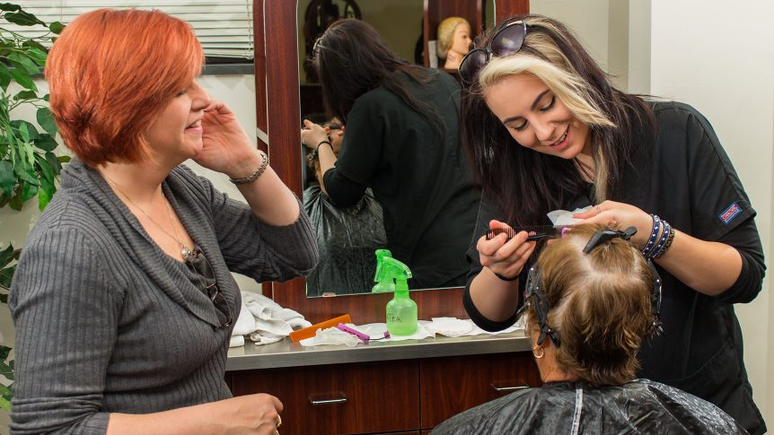 a student styles a customer's hair while the instructor looks on
