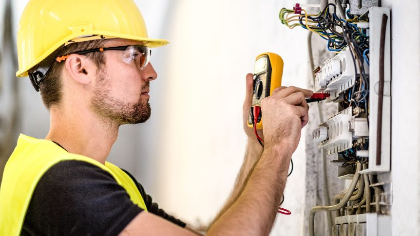 Man with a multimeter at an Industrial electric panel repair