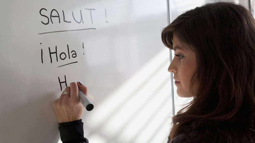 "Young woman writing ""hello"" in different languages on a white board"