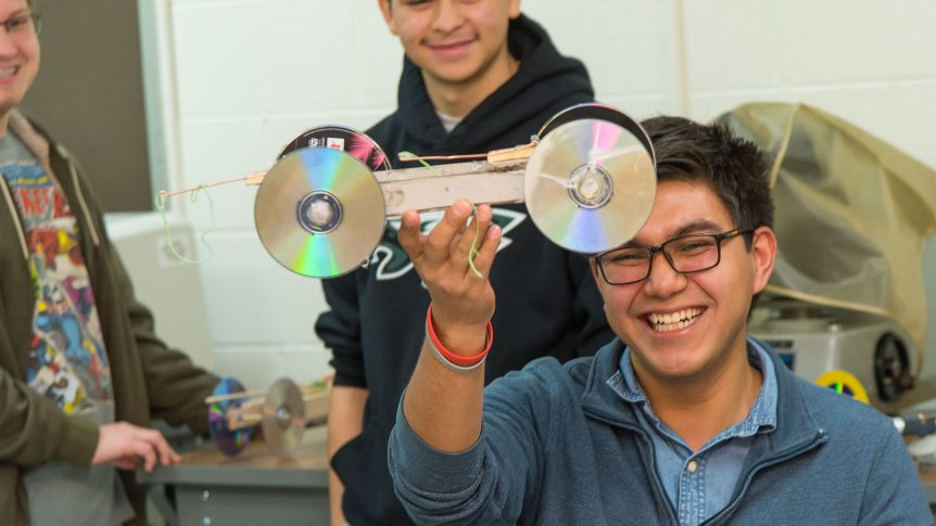 a student holds up a mousetrap-powered model car he designed