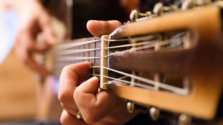 Fingers on a fretboard of a guitar