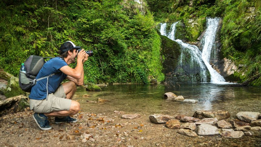 Man taking a picture of a waterfall in a lush setting