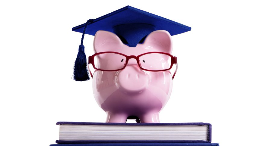 piggy bank with graduation cap and glasses standing on books