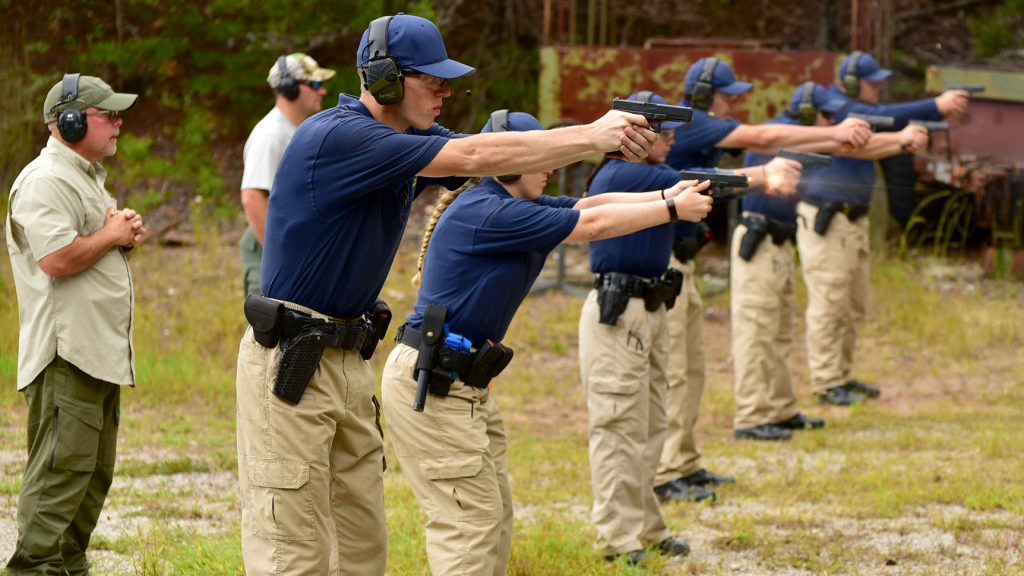 a line of B L E T students shoot their pistols on a firing range with two instructors looking on