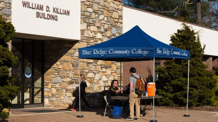 Student government association officers sit under a blue ridge community college tent outside the Killian building handing information to another student