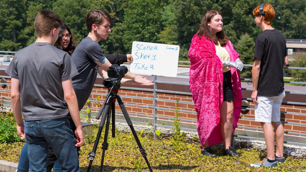 Two actors in front of a camera while film students slae the shot