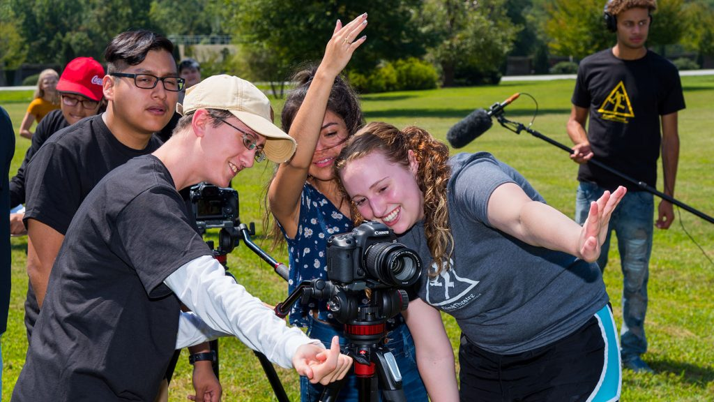 A group of students around a camera direct off-camera talent