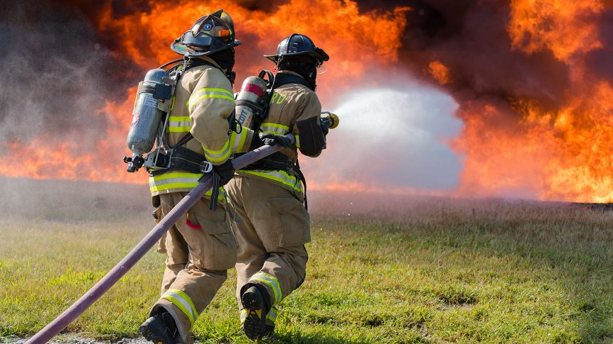 Two students in full firefighting gear charge towards a large fire with the hose spraying
