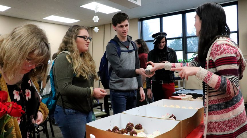 Student receives a cupcake at campus event