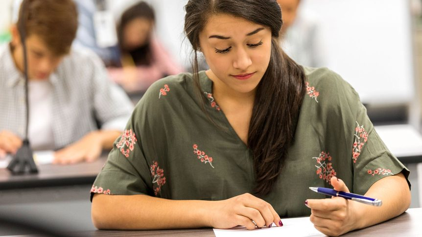 Teenage girl has a worried expression on her face while taking a math test. Students are in the background.