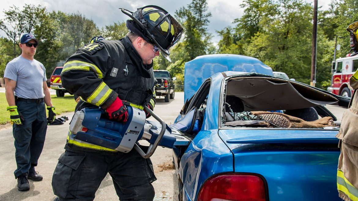 A fire and rescue student cuts the door of a wrecked car with a jaws of life