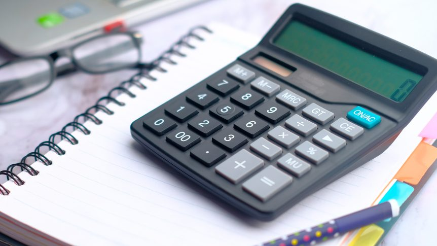 calculator on notebook with pen, eyeglasses