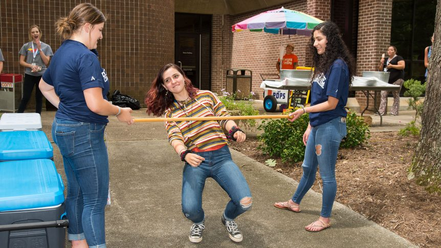 A female student begins her walk under a limbo pole while others watch