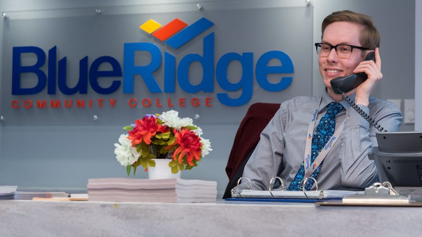 a staff member on the phone at the front desk of Blue Ridge Community College