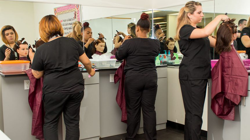 three cosmetology students practice styling hair on manikin heads
